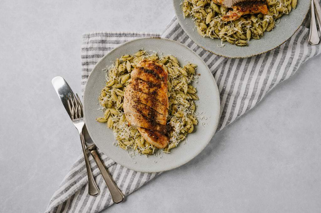 chicken and pasta on a plate with knife and fork