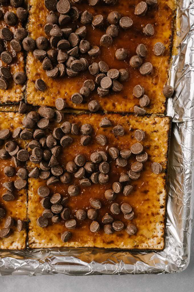 chocolate chips on hot salted matzah toffee on a foil lined baking sheet