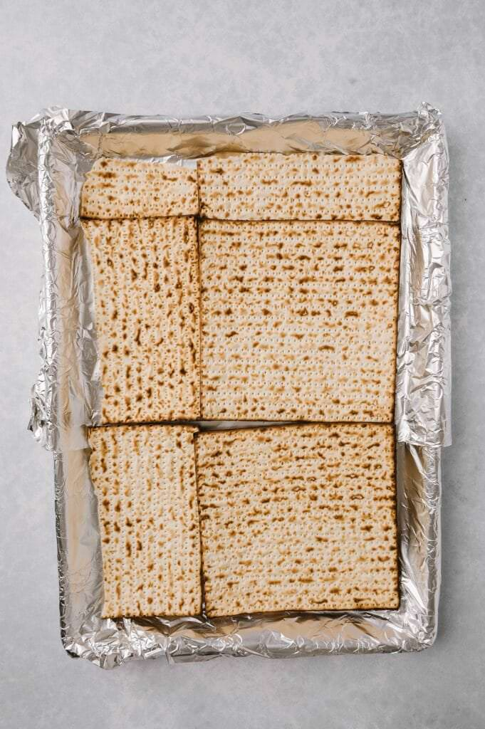 matzah laid out on a baking sheet for salted toffee matzah