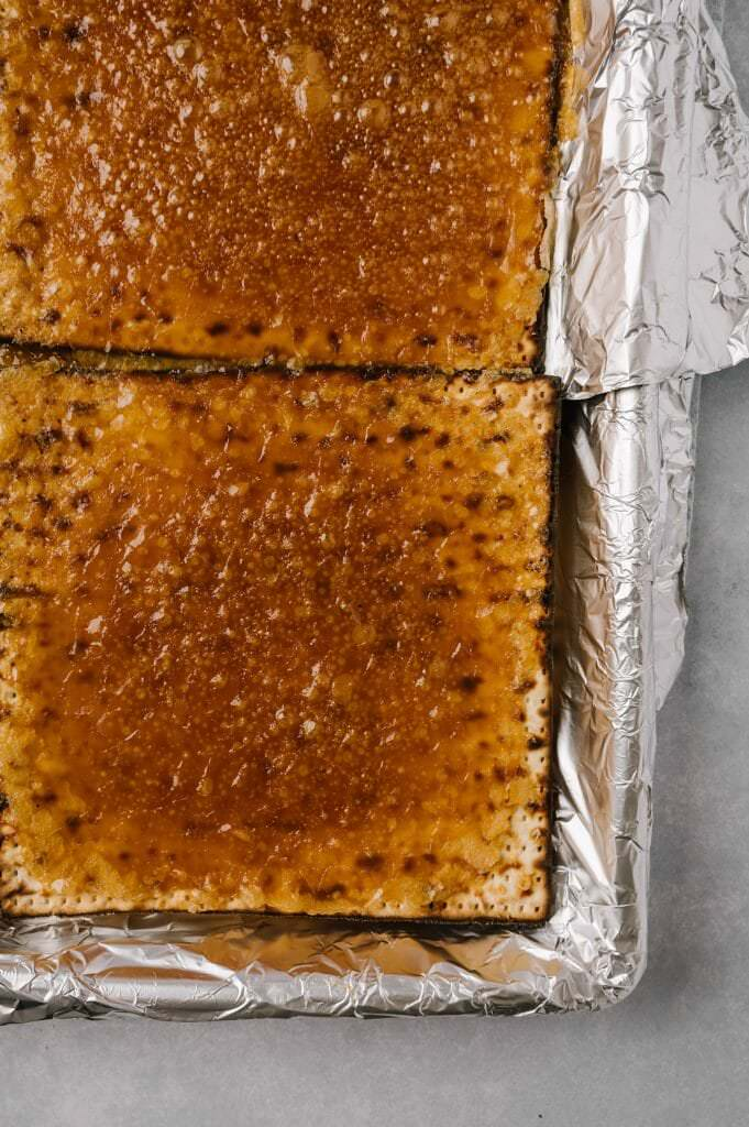 baked toffee on matzah on a foiled lined sheet pan