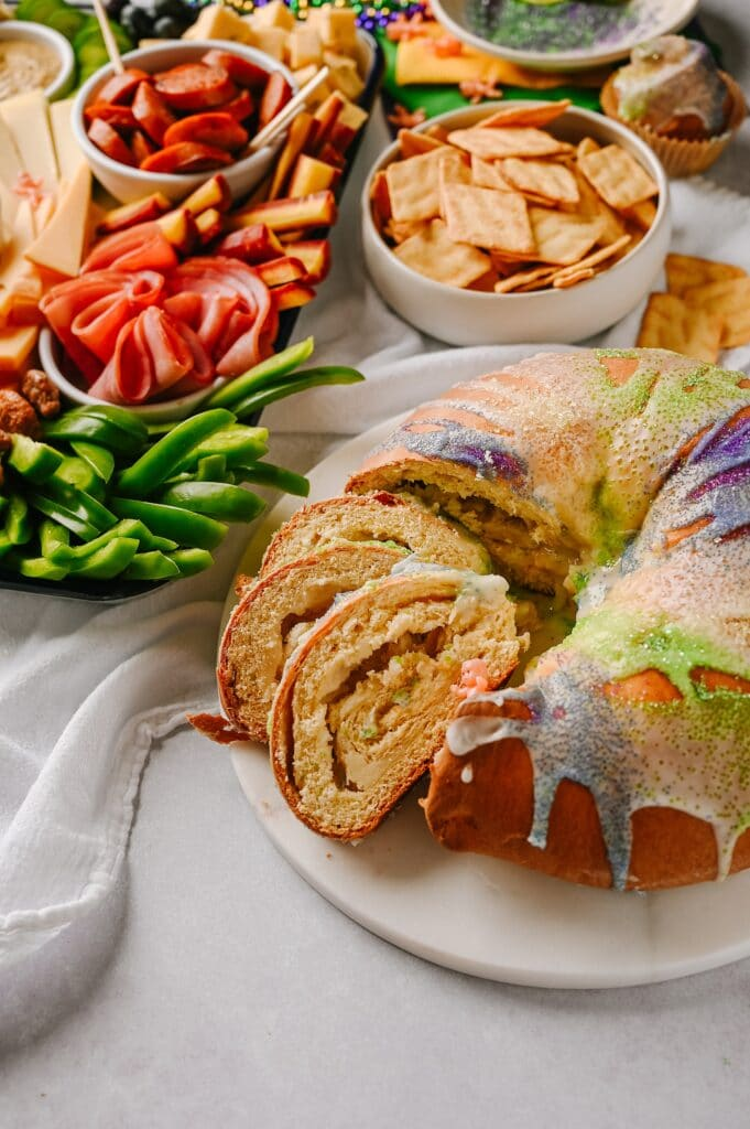 king cake with slices showing king cake baby with mardi gras inspired cheesebaord in background
