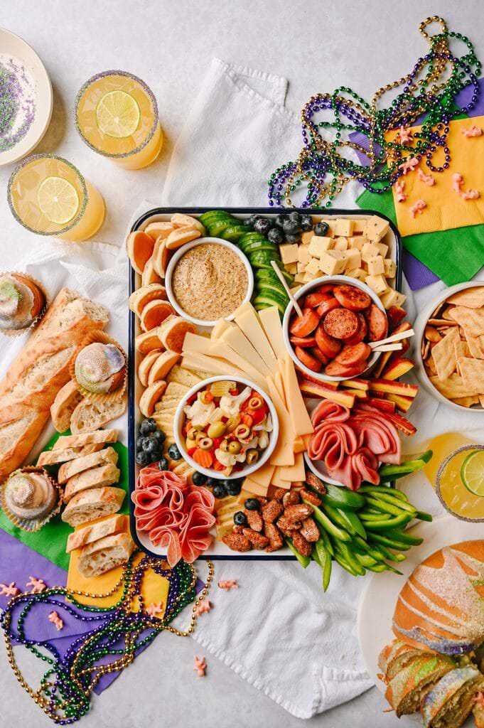 Mardi Gras-Inspired Cheeseboard with mardi gras beads king cake french bread and yellow green and purple napkins around it