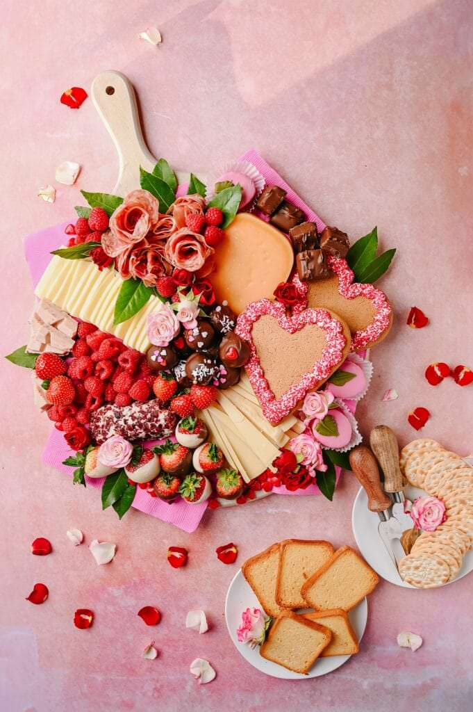 Valentine's Day Cheese and Peanut Butter Ball Board on a pink background with two plates on the side with crackers