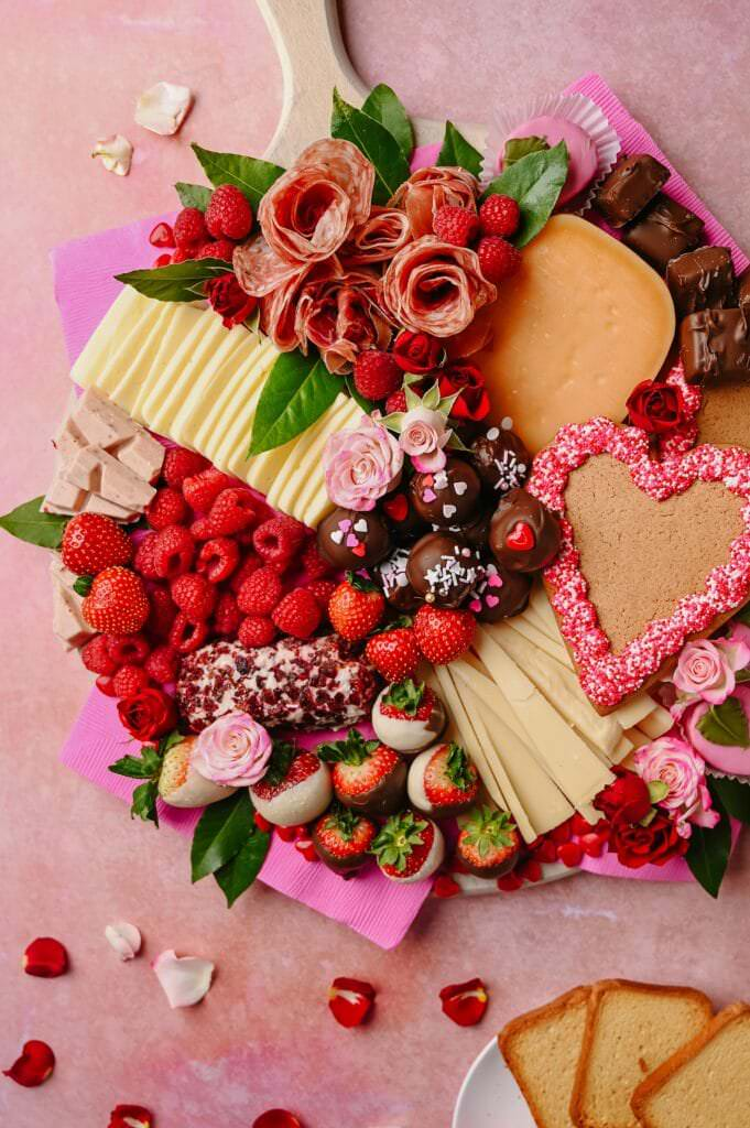 Valentine's Day Cheese and Peanut Butter Ball Board on a pink background with a plates on the side with crackers and rose petals
