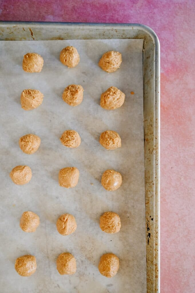 peanut butter balls portioned and chilled on a parchment lined baking sheet