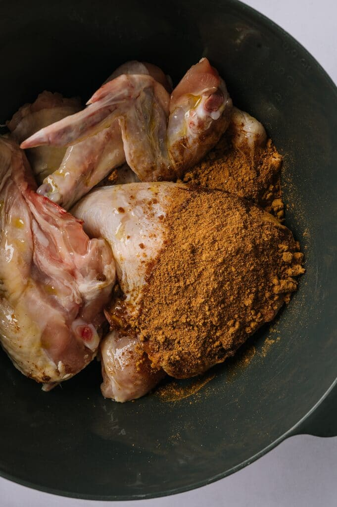 whole chicken pieces in a bowl with moroccan spice rub