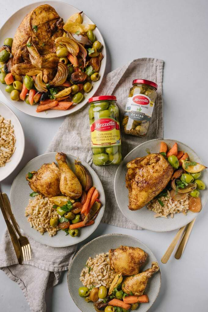 three plates of Sheet Pan Moroccan Chicken with Olives and Apricots with Israeli couscous with toasted almonds, a bowl couscous, and the platter of chicken next to two jars of olives