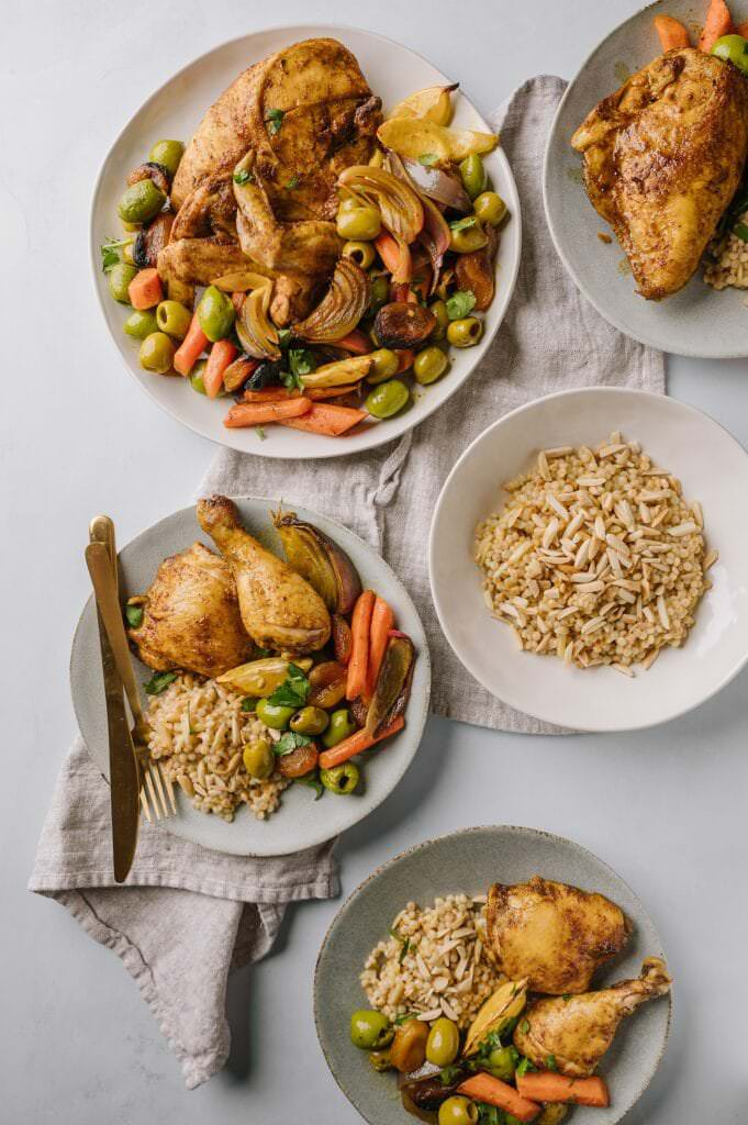 meal of Sheet Pan Moroccan Chicken with Olives and Apricots and Israeli couscous with toasted almonds on a table
