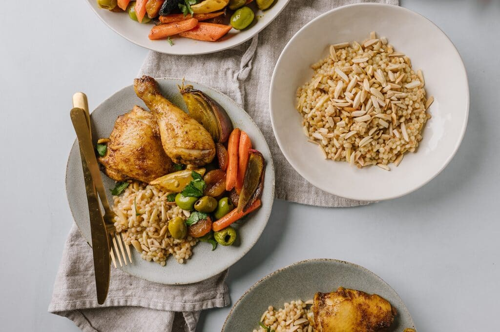 sheet pan chicken and vegetables next to a bowl of couscous