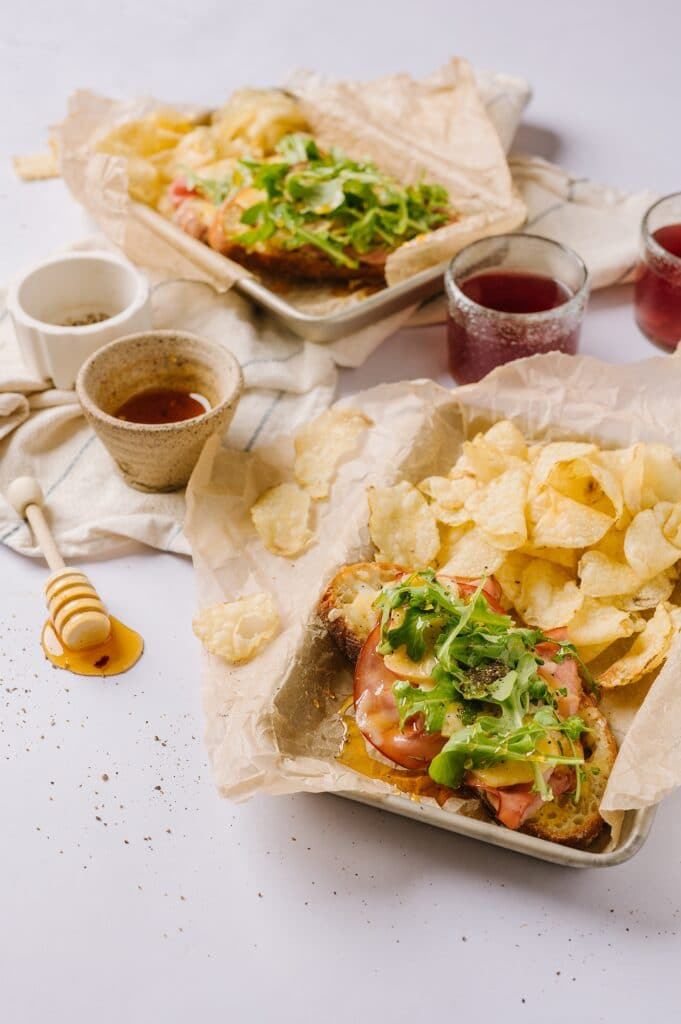 two sheets pans of sandwiches with hot honey and chips