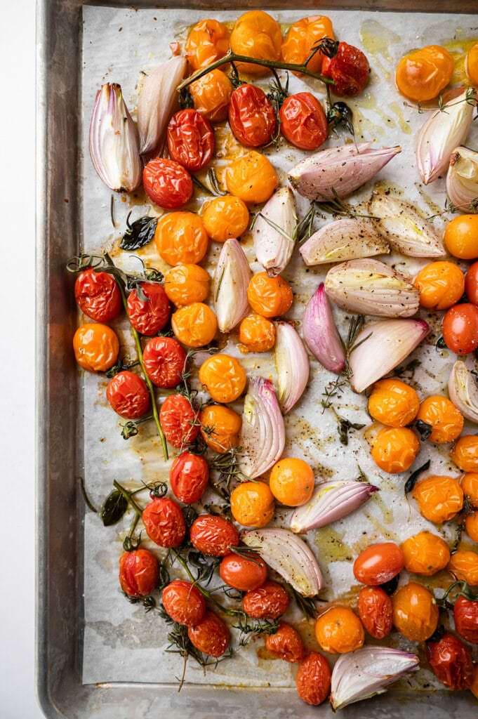 roasted tomatoes and shallots on a sheet pan