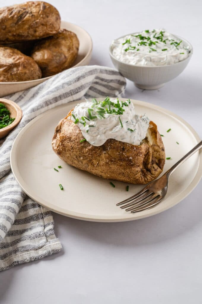 baked potato on a plate with sour cream and chives
