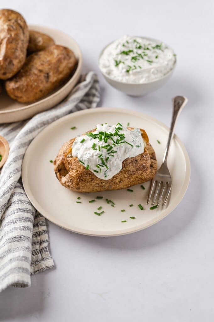 baked potato with sour cream and chives on a plate with baked potatoes, sour cream and chives in the background