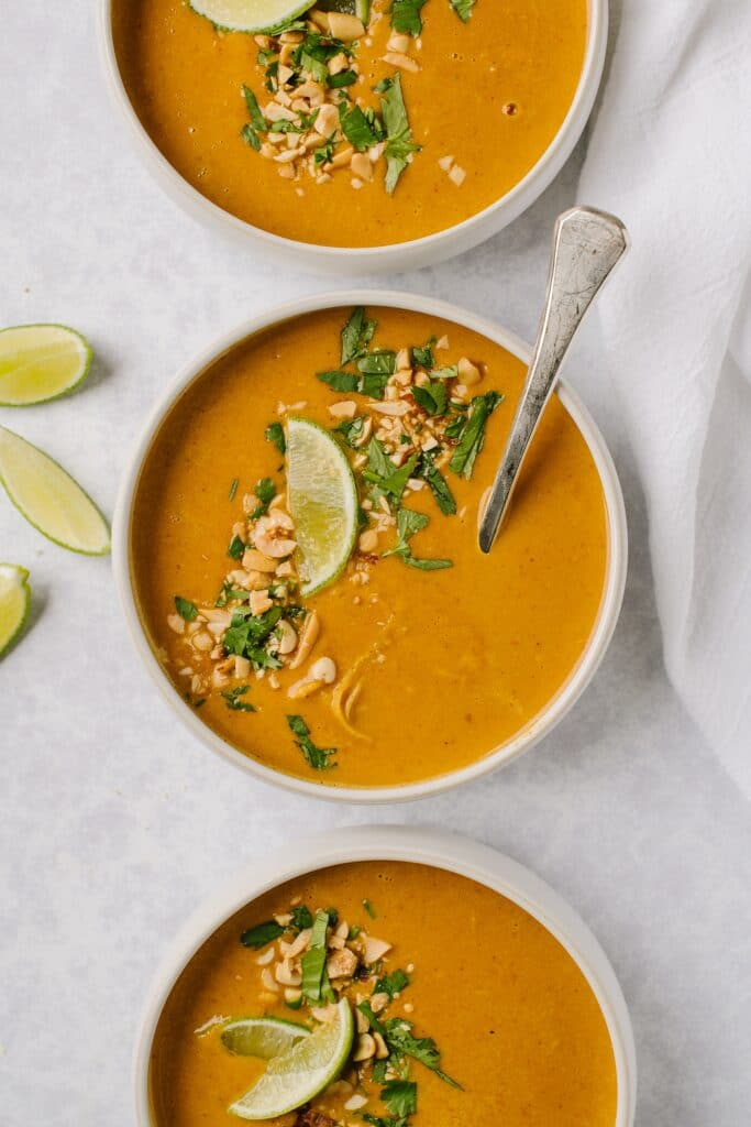bowls of chicken satay soup with limes