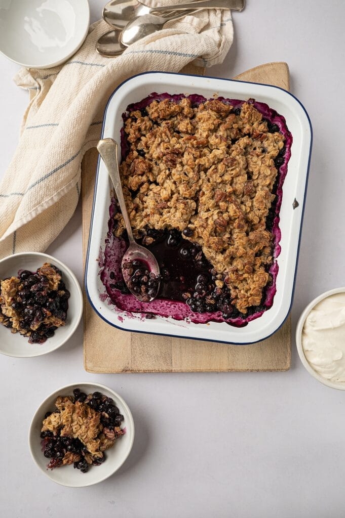 two bowls of gluten free blueberry crisp with full dish behind