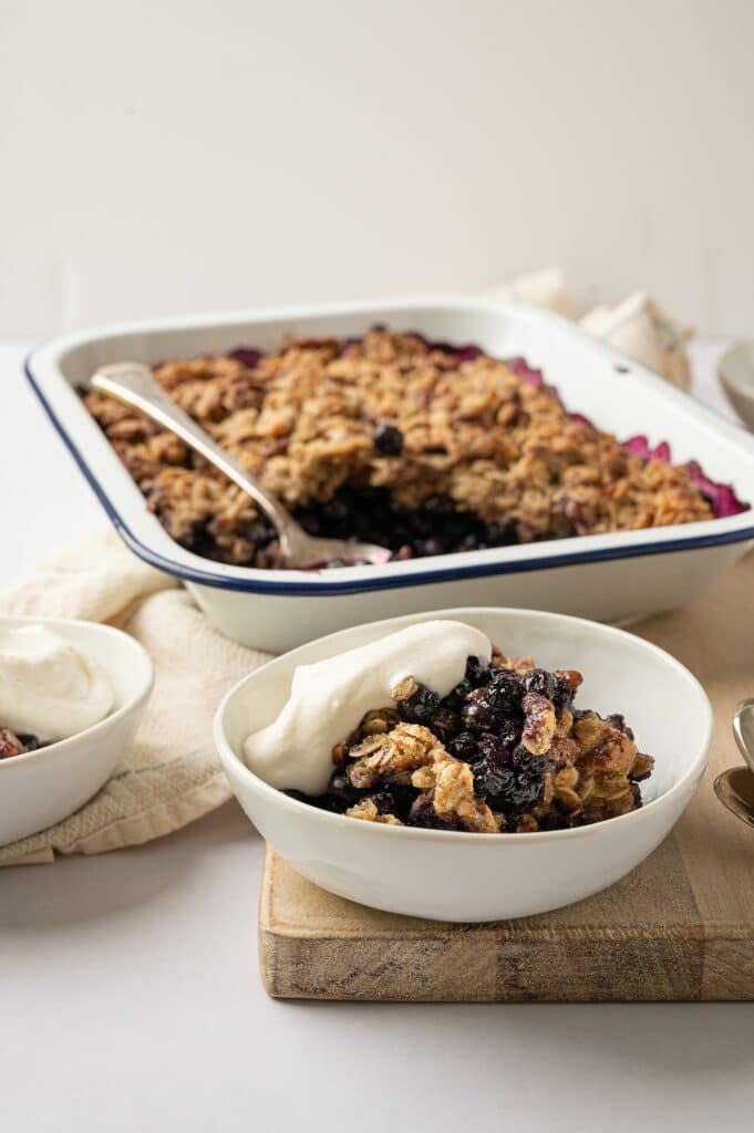 bowl of gluten free blueberry crisp with whipped cream and full dish behind it