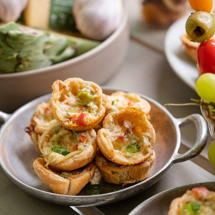 Mini Spinach and Artichoke Gouda Tarts on a silver plate