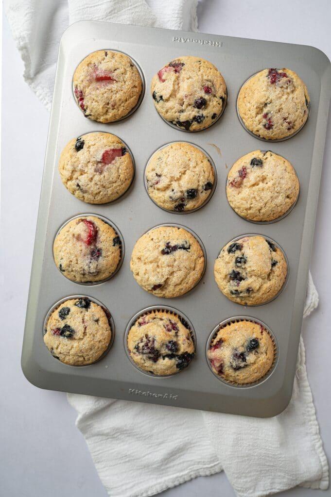 muffin pan with vegan vanilla berry muffins
