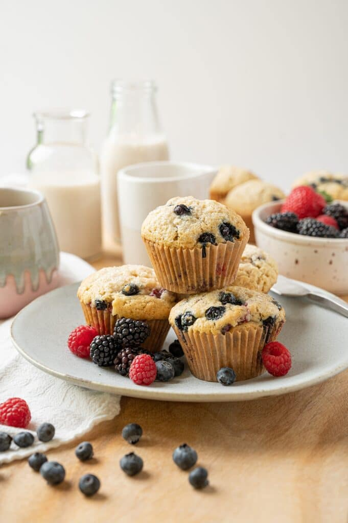 vegan vanilla berry muffins on a plate with berries and milk in the background