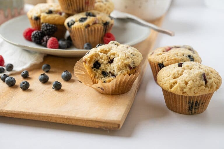 vegan vanilla berry muffin on a cutting board with berries and a plate of muffins