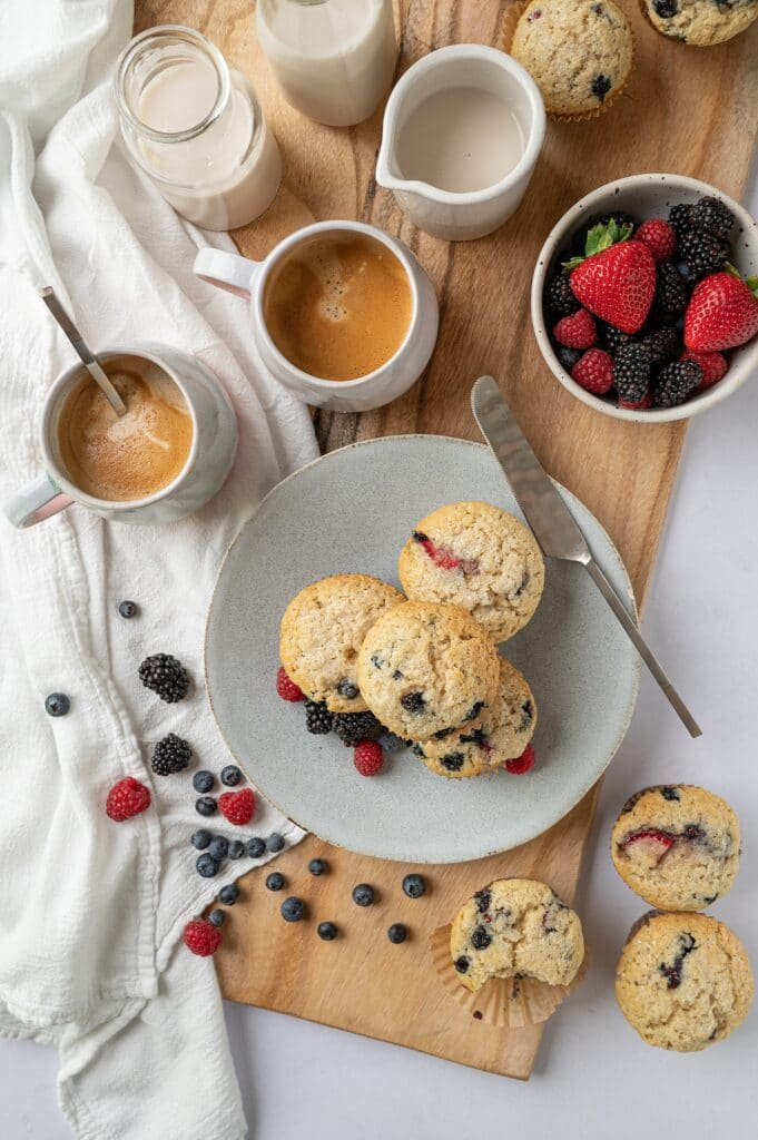 overhead view of vegan vanilla berry muffins with 2 cups of coffee and a bowl of berries