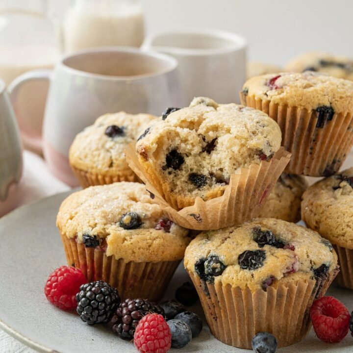 plate of vegan vanilla berry muffins with coffee cups and a bowl of berries in the background