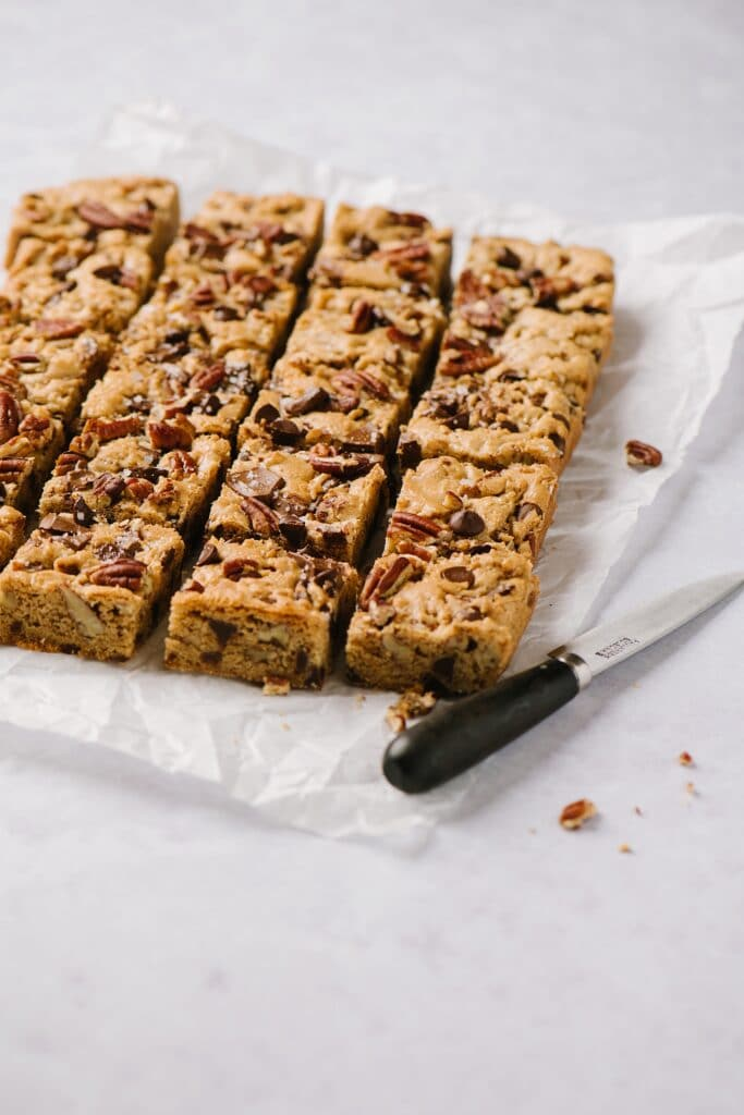 side shot of cut blondies on a sheet of parchment