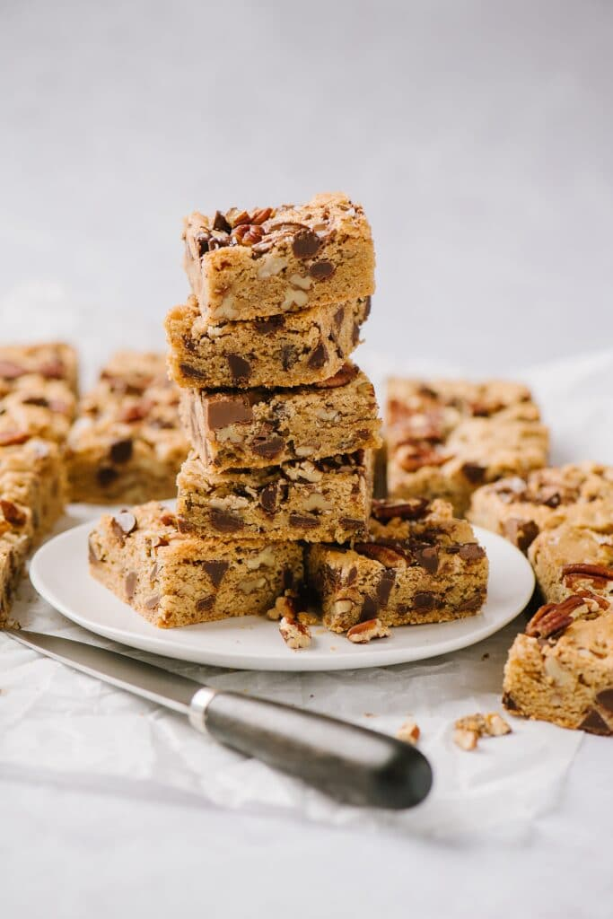 blondies stacked on top of each other on a plate with a knife on the table