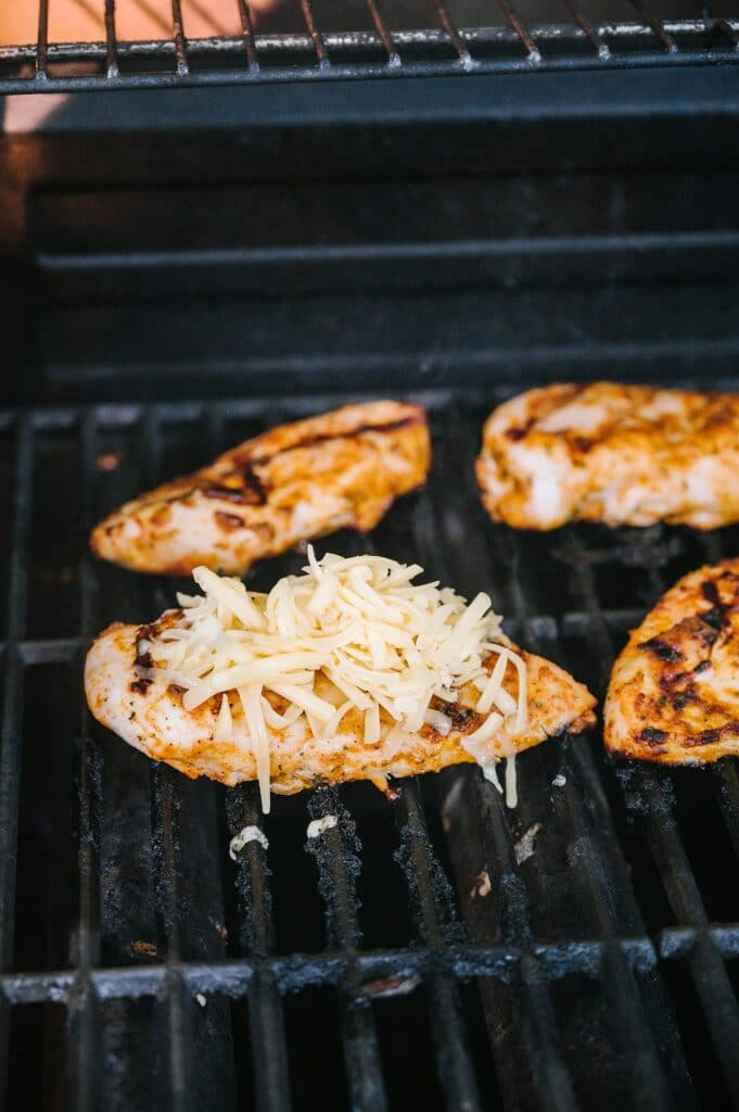 adding shredded cheese to chicken on the grill