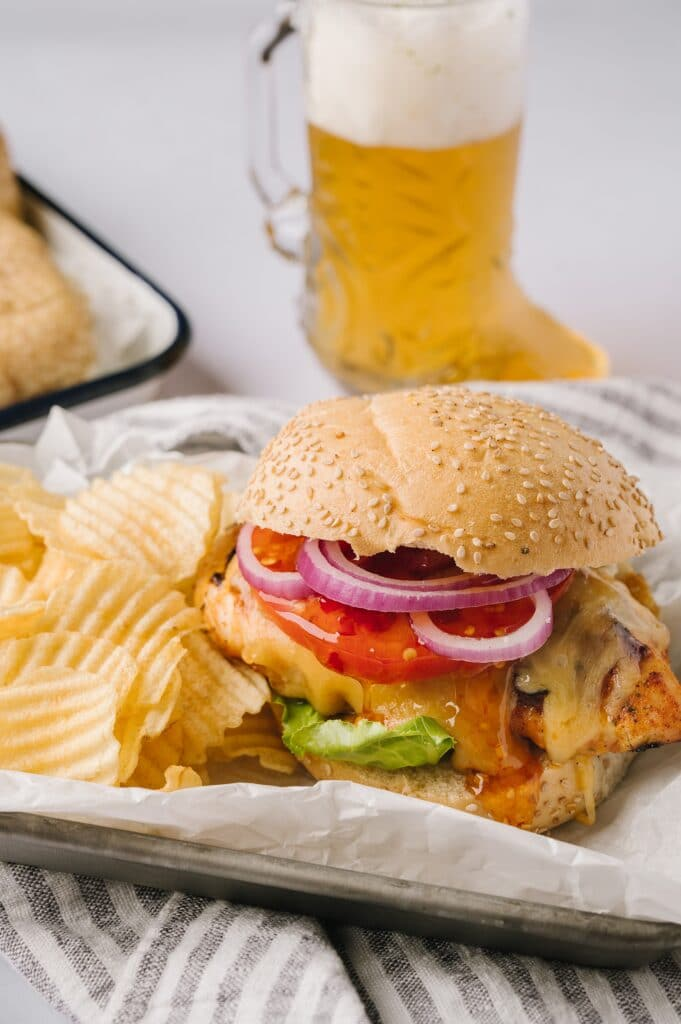 Grilled chicken sandwich and chips on a plate with a beer
