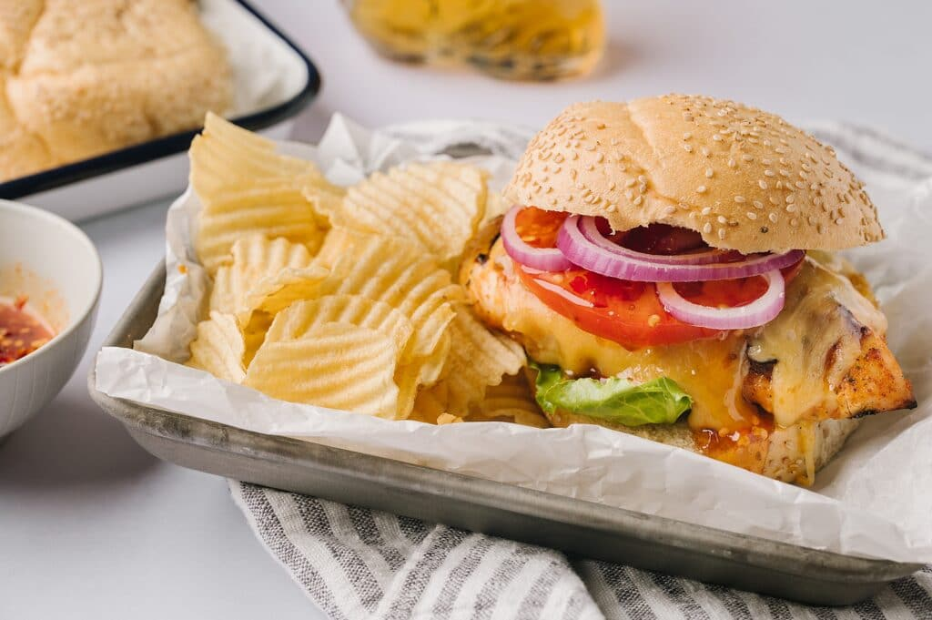 grilled chicken sandwich with lettuce tomato and onion with hot honey drizzle and chips