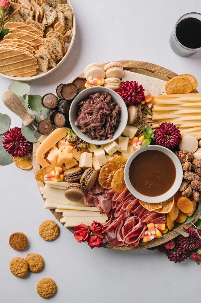 sweet and savory fall cheeseboard with crackers and glasses of red wine