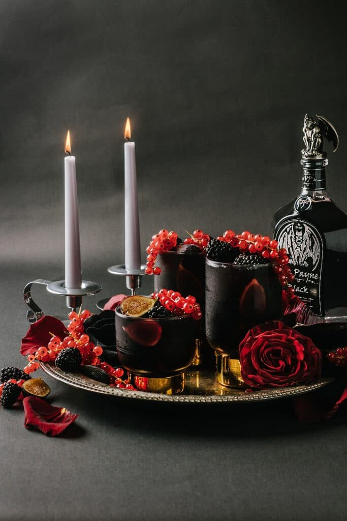 a tray of halloween drinks with candles and a bottle in the background
