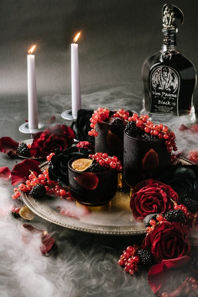 black currant haloween sangria on a platter with roses, berries, and figs with candlesticks, dry ice, and Von Payne Black