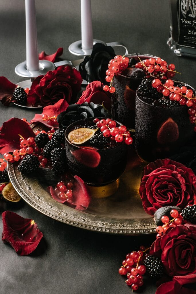 halloween cocktail on a tray with roses and candles