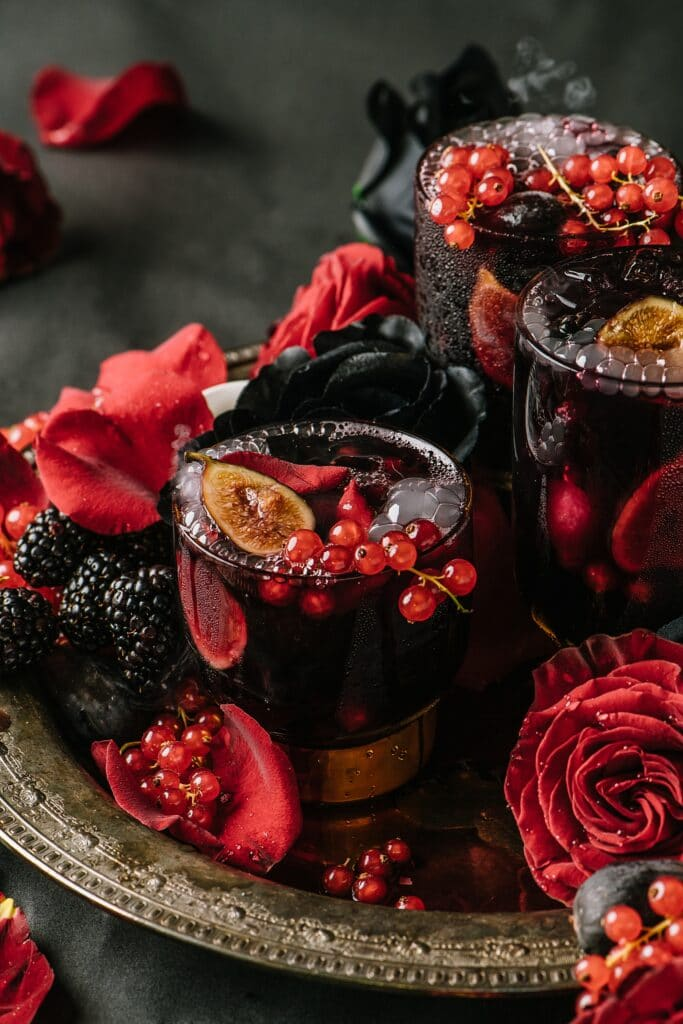 glass of halloween sangria on a tray surrounded by roses, currants, and blackberries