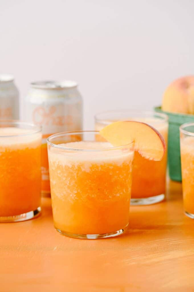 frozen ginger peach bellinis in a glass with a peach slice