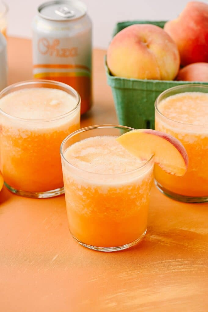 frozen ginger peach bellini in a glass with peach slices and Ohza in the background